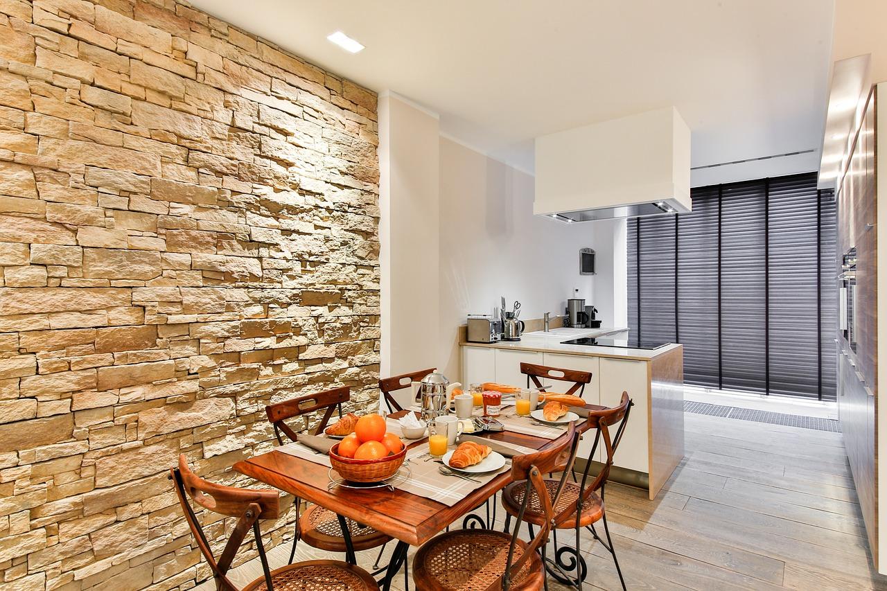 Kuchyně a jídelna by měly být dostatečně osvětlené. Při výběru světla nad kuchyňský stůl ale volte spíše žluté odstíny žárovky. Je příjemnější očím a nezkreslují barvu jídla.