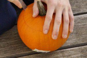 Při dlabání dýně nejprve opatrně ostrým nožem odřízněte ve vrchní části kulatý otvor. Tím pak budete dlabat ven dužninu.