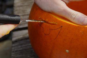 Ostrým nožem začněte vyřezávat strašidláka. Je dobré si motiv na dýni předkreslit.